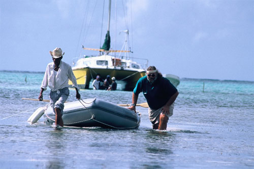 Xcalak, Mexico, Xpat, Richard pulling the boat to shore after Hurricane Mitch grounded her. He was headed to Belize when hurricane struck.